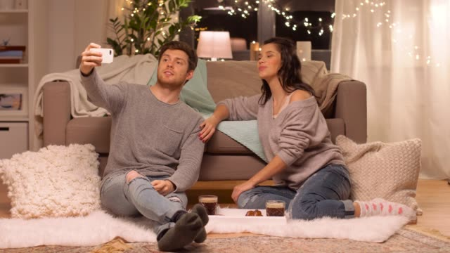 vídeos de stock e filmes b-roll de happy couple taking selfie by smartphone at home - hygge