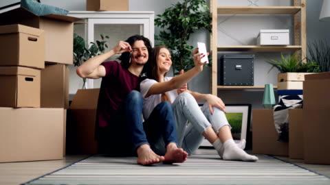 vidéos et rushes de couples heureux prenant le selfie avec des clefs utilisant l'appareil-photo de smartphone dans l'appartement neuf - jeune couple