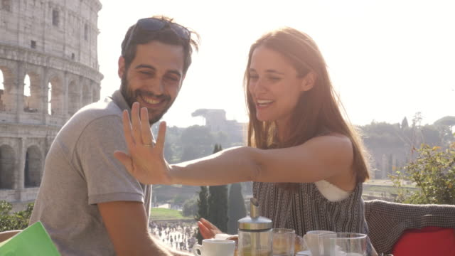 Happy couple taking selfies with marriage proposal ring at restaurant in front of colosseum in rome at sunset video