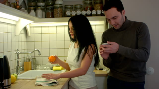 Happy couple talking and using smartphone while cooking in kitchen at home video