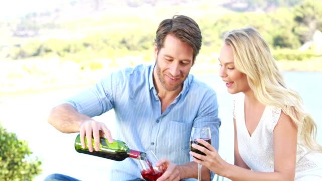 glückliches paar anstoßen und trinken rotwein - rotwein stock-videos und b-roll-filmmaterial