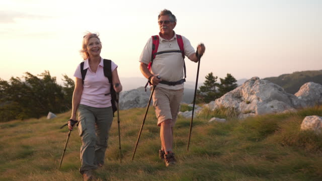 happy couple trekking on a mountain - trekking video stock e b–roll
