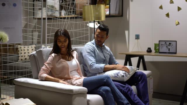 vídeos de stock, filmes e b-roll de casal feliz enquanto fala a experimentar um sofá em uma loja de móveis - mobília