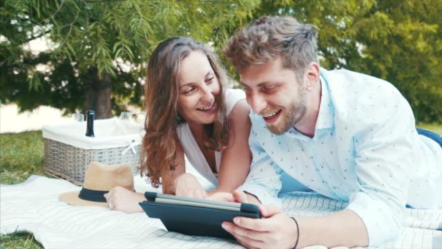 Feliz pareja utilizando una tableta digital. - vídeo