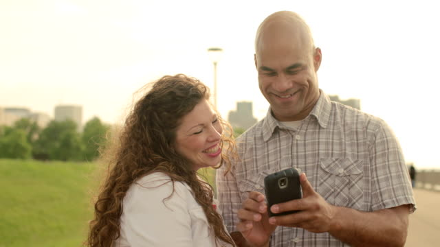 Happy couple using a smart phone in Detroit video