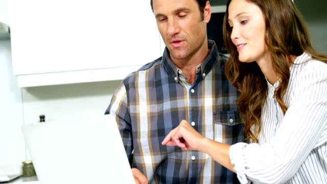 happy couple using laptop - quarantenne video stock e b–roll