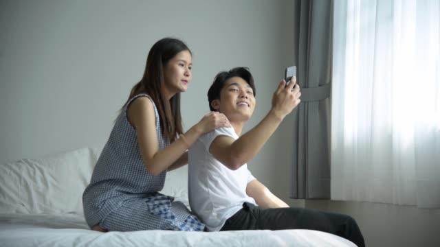 自分撮りやビデオ通話に携帯電話を使用して幸せなカップル - スマホ ベッド点の映像素材/bロール
