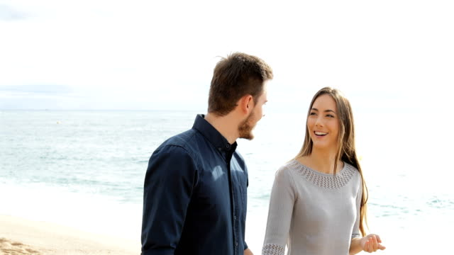 happy couple walking and talking on the beach - vivere semplicemente video stock e b–roll