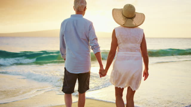 happy couple walking on the beach at sunset - retirement stock videos and b-roll footage