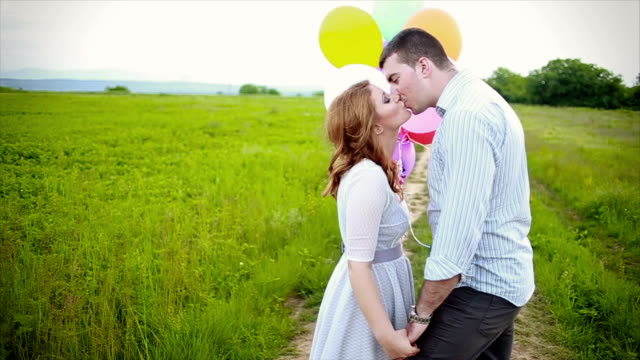 Happy couple walking through the field with balloons video