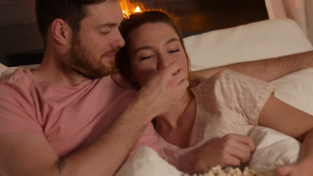 happy couple watching tv in bed at night at home - vídeo