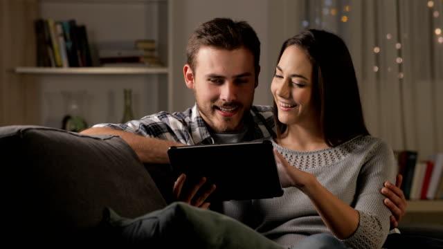 vídeos y material grabado en eventos de stock de feliz pareja viendo videos en una tableta en la noche - descargar internet