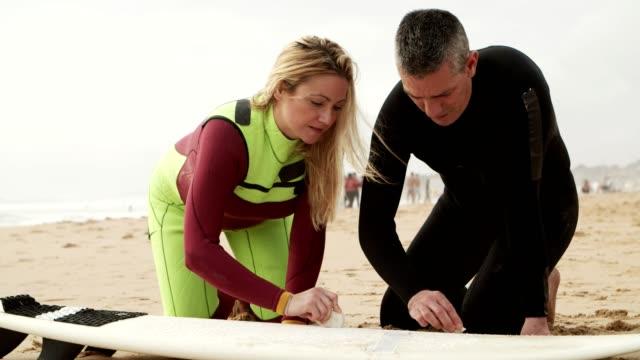glückliches paar wachsende surfbrett am strand - wachs epilation stock-videos und b-roll-filmmaterial
