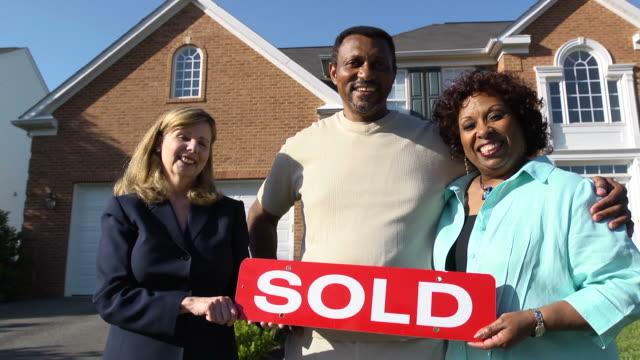coppia felice con agente holding venduto segno - vendere video stock e b–roll