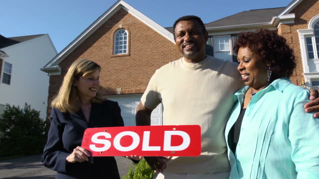 Happy Couple with Agent Holding SOLD Sign video