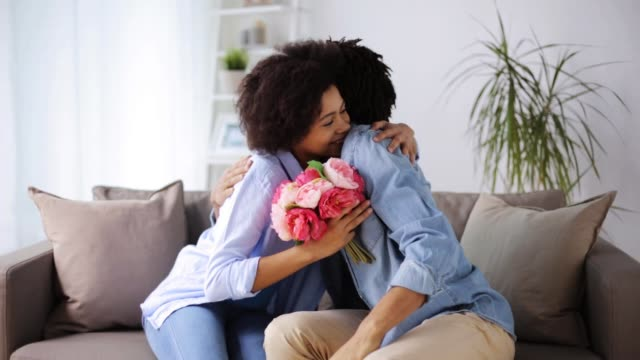 happy couple with bunch of flowers at home video