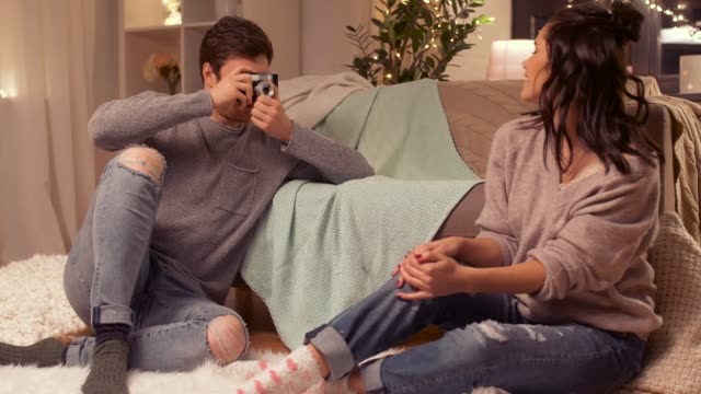 vídeos de stock e filmes b-roll de happy couple with camera photographing at home - hygge