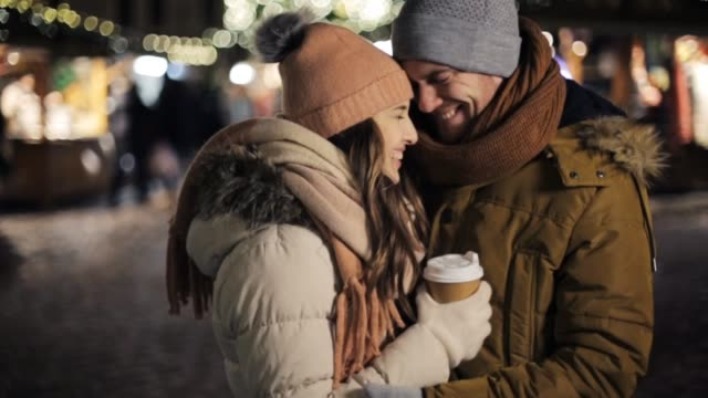 happy couple with coffee at christmas market winter holidays, hot drinks and people concept - happy young man bringing coffee in disposable paper cup for his woman at christmas market in evening boyfriend stock videos & royalty-free footage