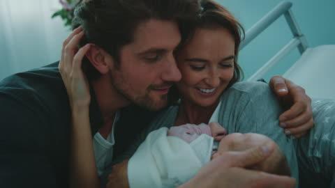 stockvideo's en b-roll-footage met gelukkige paar met pasgeboren baby in ziekenhuis - gewone snelheid