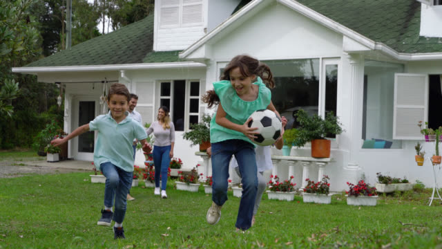 Happy couple with their two daughters and son walking behind them as they run excited ready to play Happy couple with their two daughters and son walking behind them as they run excited ready to play - Lifestyles facade stock videos & royalty-free footage