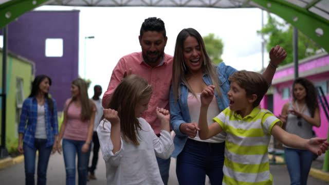 lyckliga paret med sina två barn att ange en nöjespark som är mycket entusiastiska och andra människor som gick bakom dem. - fritidsanläggning bildbanksvideor och videomaterial från bakom kulisserna