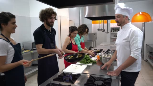 vídeos de stock e filmes b-roll de happy couples at a cooking class and head chef teaching them checking what they are doing - aprender