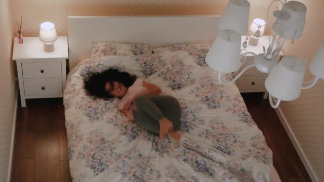 Happy Curly young woman falls on the bed in room video