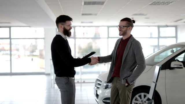 A happy customer Young and handsome hipster man, buying a new car from the car saloon. car salesperson stock videos & royalty-free footage