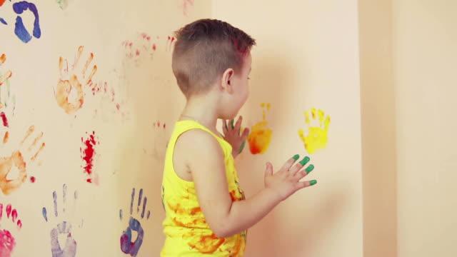 glad söt liten pojke har kul lämnar hans färgglada handavtryck på väggen. unga lycklig familj. mor och barn koncept. slowmotion - painting wall bildbanksvideor och videomaterial från bakom kulisserna