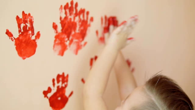 Happy cute little boy is having fun leaving his red handprints on the wall. Young happy family. Mother and child concept. Slowmotion