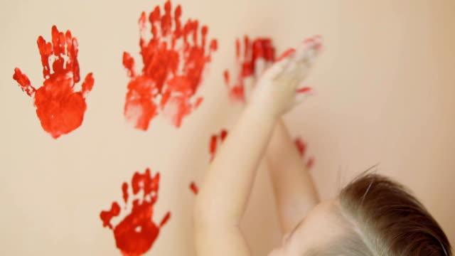 glad söt liten pojke har kul lämnar hans röda handavtryck på väggen. unga lycklig familj. mor och barn koncept. slowmotion - painting wall bildbanksvideor och videomaterial från bakom kulisserna