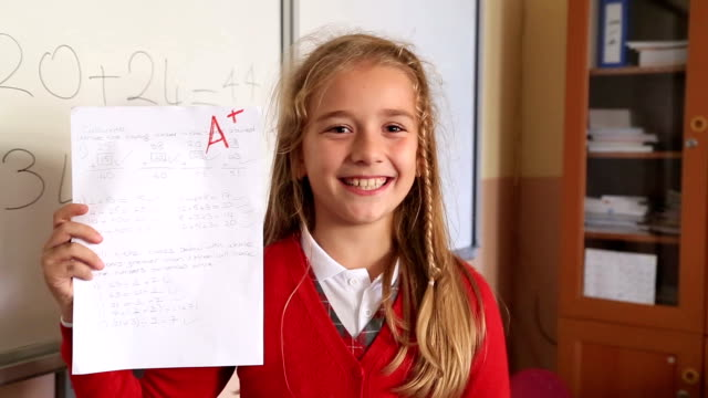 Happy cute little girl showing exam paper with a plus in the classroom
