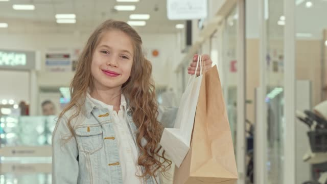 Happy cute little girl showing thumbs up at the shopping mall