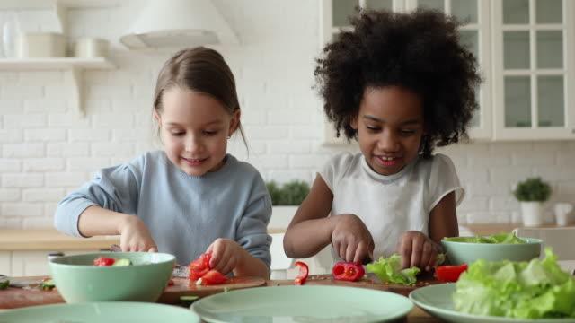 Happy cute little mixed race children chopping fresh vegetables.