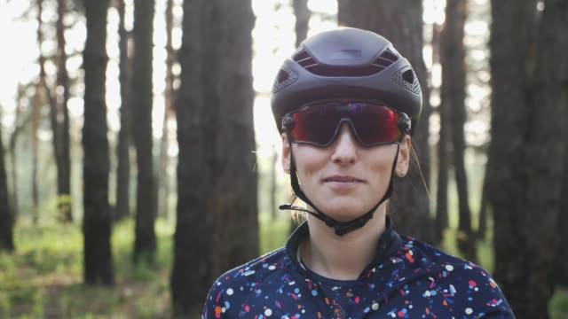 happy cycling girl sfreccia in maglia blu prima di allenarsi indossando casco e occhiali neri. concetto di ciclismo - pantaloncini video stock e b–roll