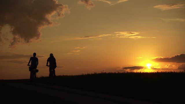 glada cyklister vid solnedgången - bergsrygg bildbanksvideor och videomaterial från bakom kulisserna