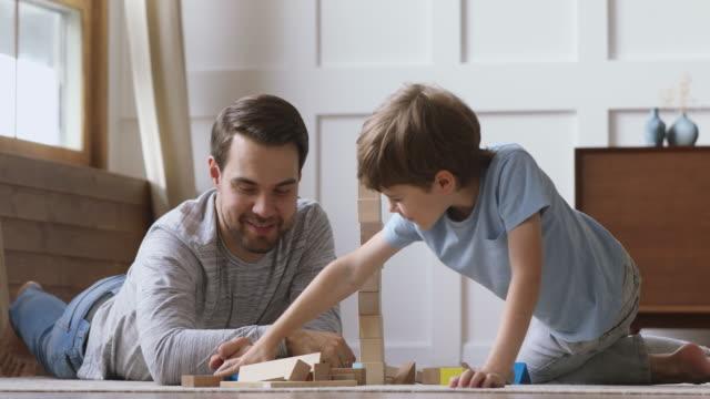 lycklig pappa hjälpa barn son byggnad slott av träklossar - förskoleelev bildbanksvideor och videomaterial från bakom kulisserna
