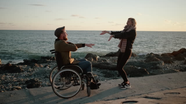 Happy dance of the girl and her disable boyfriend Disabled man and his cheerful girlfriend enjoying time together and dancing. Having fun on walk by the sea at sunset girlfriend stock videos & royalty-free footage