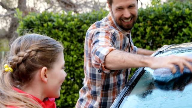 Fille heureuse et père lavage voiture avec éponge 4K 4k - Vidéo