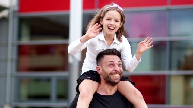 Una hija feliz de una alumna se sienta sobre los hombros de su joven padre. La chica está agitando alegremente las manos. Día de padres - vídeo