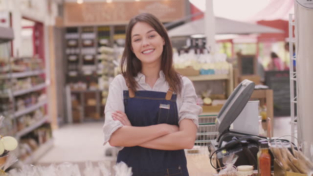 Happy deli owner standing with arms crossed at checkout counter Handheld shot of happy deli owner standing at checkout counter. Portrait of smiling young saleswoman is with arms crossed in store. She is wearing denim overalls. 4K Resolution. saleswoman stock videos & royalty-free footage