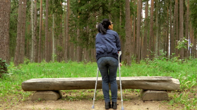 Happy disabled female with crutches near bench in park Happy disabled female with crutches near bench in park crutch stock videos & royalty-free footage