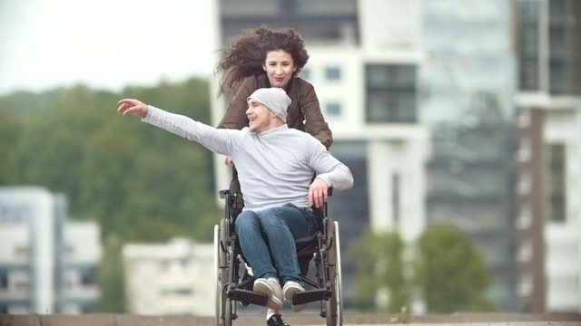Happy disabled man in a wheelchair with happy young woman running at the city street Happy disabled man in a wheelchair with happy young woman running at the city street, slow motion disability stock videos & royalty-free footage