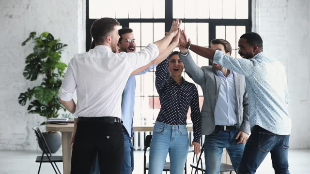 Happy diverse business team give high five together, slow motion Happy diverse professional business office team give high five together in office, multiethnic coworkers group celebrate corporate success engaged in unity teamwork partnership concept, slow motion stimulus stock videos & royalty-free footage