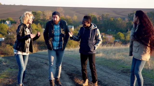 Heureux groupe diversifié, marchant sur le chemin de terre - Vidéo
