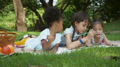 Happy Diverse Kids painting Close up of Happy Diverse Kids painting and relaxing in the garden. art and craft stock videos & royalty-free footage