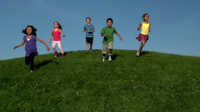 happy diverse kids running down grassy hill in slow motion - jogging hill bildbanksvideor och videomaterial från bakom kulisserna