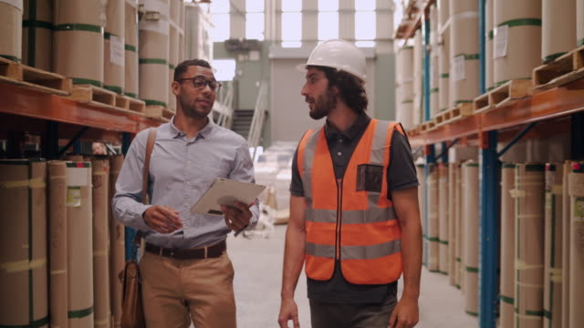 Happy diverse warehouse management team shaking hands after checking distribution in storage house
