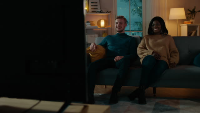 vídeos de stock e filmes b-roll de happy diverse young couple watching comedy on tv while sitting on a couch, they laugh and enjoy show. handsome caucasian boy and black girl in love spending time together in the cozy apartment. - tv e familia e ecrã