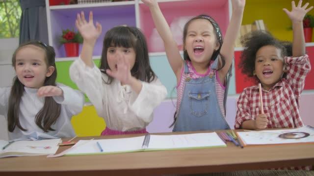 lycklig mångfald barn händer stiga upp och kram tillsammans med fullt leende, barnen leker i vardags rummet hemma, tilt upp och zooma ut skott. - förskoleelev bildbanksvideor och videomaterial från bakom kulisserna